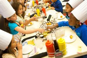 First grade students from Robert E. Lake Elementary School enjoy some delicious food after learning how to prepare them inside the kitchen at I Love Burgers, Thursday March 29, 2012. The students are participating in a program called First Grade Food Critics which designed to promote nutrition education and academic development.