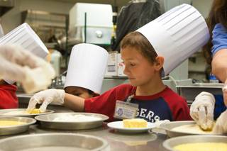 Chef Crisafulli instructs a group of first grade students from Robert E. Lake Elementary School on how to prepare some macaroni bites in the kitchen at I Love Burgers inside the Shoppes at the Palazzo Thursday March 29, 2012. The students are participating in a program called First Grade Food Critics which designed to promote nutrition education and academic development.