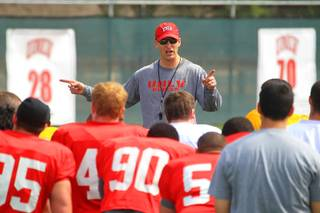 Coach Bobby Hauck talks to his team during football practice March 30, 2012.