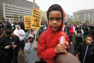 Isaiah Henry-Simpson, 7, of Arlington, Va., eats Skittles candy while attending a rally with his parents in support of Trayvon Martin at Freedom Plaza in Washington, on Saturday, March 24, 2012. Many people in attendance brought candy, ice tea, and wore hooded sweatshirts, or hoodies, in support of the unarmed young black teen, who was fatally shot by a volunteer neighborhood watchman.