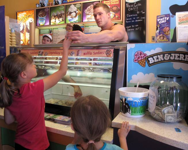Chippendale Kyle Efthemes hands a sweet treat to Sydney Kellar, 7, at Ben & Jerry's at The District. It was free-cone day to celebrate the company's 34th anniversary.