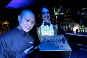 The Gazillionaire presents golden alligator shoes to Tony Hsieh.