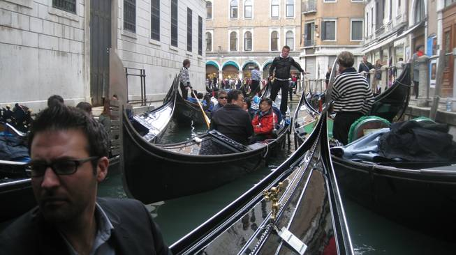A gondola is navigated through a busy canal in Venice. The guy in the foreground is Tony Moreno.