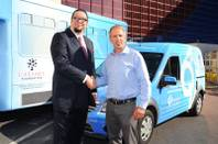 Penn Jillette with Thom Reilly, executive director of Caesars Foundation, in front of the two vehicles purchased using a portion of the $250,000 donated by Caesars Foundation to Opportunity Village.