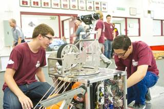 Chad Pesquera, at left, and Joseph Mauro of Cimarron Memorial High School work on their competition robot