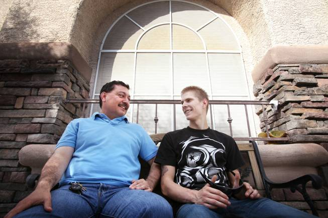 "Matthew Pitzer, right, 18, sits with Manny Solario at Solario's home in Las Vegas on Friday, April 27, 2012. Pitzer was 12 when he walked into Solario's special education class; today he calls Solario ""dad."""