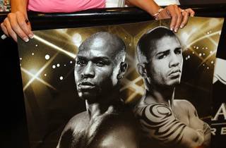 A fan holds a poster featuring Floyd Mayweather Jr., left, and WBA super welterweight champion Miguel Cotto during official arrivals in the lobby of  the MGM Grand Tuesday, May 1, 2012. Mayweather  will challenge Cotto of Puerto Rico at the MGM Grand Garden Arena on Saturday. STEVE MARCUS