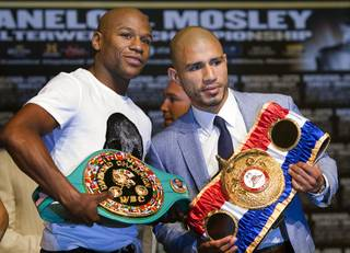 Undefeated boxer Floyd Mayweather Jr. and WBA super welterweight champion Miguel Cotto of Puerto Rico pose during a news conference at the MGM Grand Wednesday, May 2, 2012. Mayweather will challenge Cotto for the title at the MGM Grand Garden Arena on Saturday.