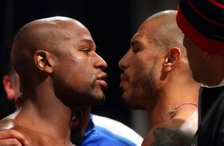 Floyd Mayweather Jr., left, and WBA super welterweight champion Miguel Cotto of Puerto Rico face off during their official weigh-in at the MGM Grand Garden Arena Friday, May 4, 2012. Mayweather will challenge Cotto for the title at the arena Saturday.