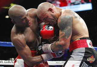 Floyd Mayweather Jr., left, battles it out with WBA super welterweight champion Miguel Cotto of Puerto Rico during their title fight at the MGM Grand Garden Arena Saturday, May 5, 2012.