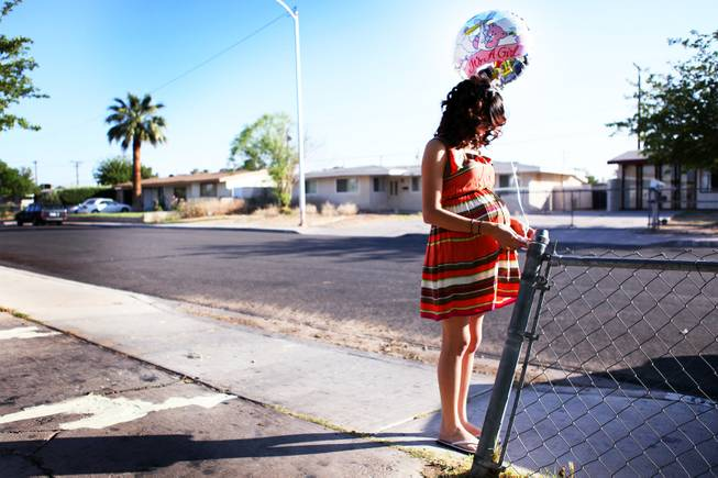 Evaleen Diaz ties a balloon at the end of her driveway during her baby shower at her home in Las Vegas on Saturday, May 5, 2012.