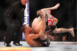 Nate Diaz, bottom, sinks in the fight-winning choke against Jim Miller during the second round of their lightweight bout at UFC on Fox at the Izod Center in E. Rutherford, N.J., on Saturday, May 5, 2012. Diaz won via tapout due to the choke in round 2.