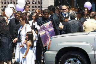 A man is seen carrying Yadira Martinez's portrait after the funeral service held for Martinez and her daughter Karla at St. Christopher Catholic Church on Friday, May 11, 2012.