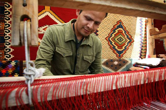 "Antonio Mendoza, 38, of Orange County, Calif., demonstrates on a loom how he weaves his handmade tapestries, blankets and other products. Mendoza said he focuses on collectors more now than before the recession because they are the ones who are ""not afraid to spend"" on art these days."