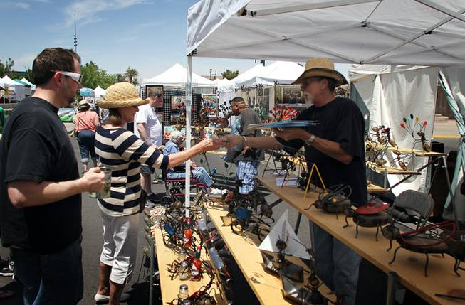 Jeffrey Newmark of Laughlin sells one of his Garden Critters, animal sculptures made from wire, stones and other materials, to