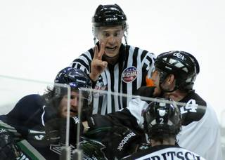 ECHL referee TJ Luxmore dishes out a two-minute penalty as players skuffle in front of him near the end of the second period of Game 1 of the Kelly Cup Finals at the Orleans Arena on Monday night.