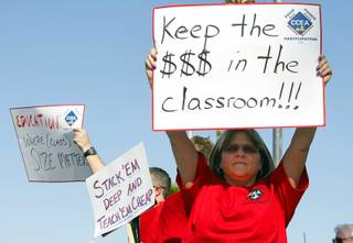 Debra Cooley, a kindergarten teacher at Steele Elementary School, holds up a sign before a Clark County School Board meeting at the Edward Greer Education Center on East Flamingo Road Wednesday, May 16, 2012. The board approved a final budget that will lay off 1,015 positions in order to balance the budget.