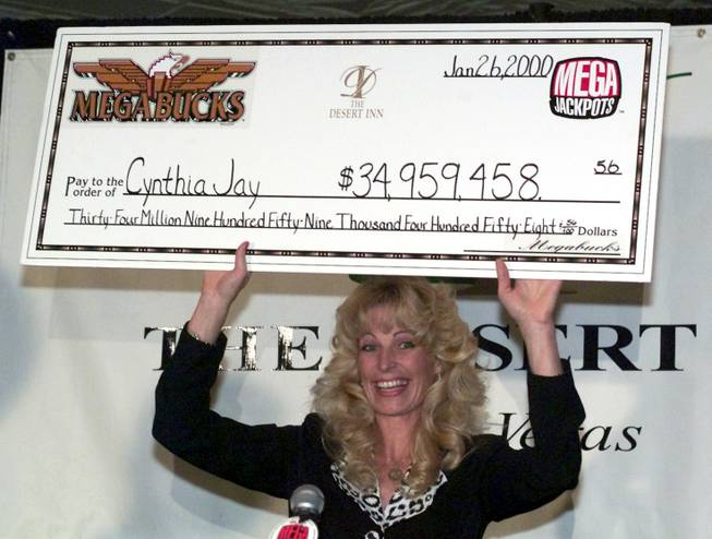 Cynthia Jay holds up an oversized check at the Desert Inn Thursday, January 27, 2000. Jay won a record Megabucks jackpot for $34,959,458.56 on Wednesday at the hotel-casino. It is the world's largest jackpot ever hit on a slot machine. Jay invested $27 before hitting the jackpot on her last spin.