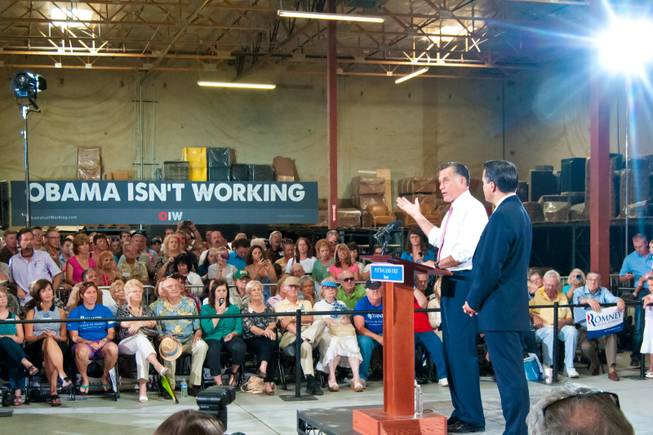 Presidential hopeful Mitt Romney, and Nevada Governor Brian Sandoval at right, address supporters during a campaign rally at a local business, Tuesday May 29, 2012.