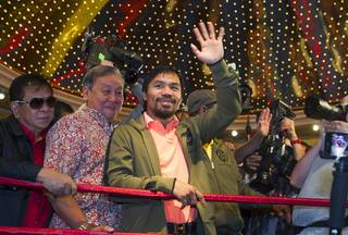 Boxer and Filipino congressman Manny Pacquiao waves to fans as he arrives at the MGM Grand Tuesday, June 5, 2012. Pacquiao will defend his WBO welterweight title against undefeated boxer Timothy Bradley Jr. at the MGM Grand Garden Arena Saturday.