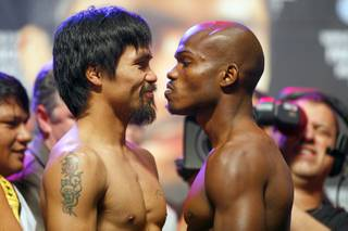 Filipino boxer Manny Pacquiao, left, and Timothy Bradley Jr. face off during an official weigh-in at the MGM Grand Garden Arena Friday, June 8, 2012. Pacquiao will defend his WBO welterweight title against the undefeated Bradley at the arena on Saturday.