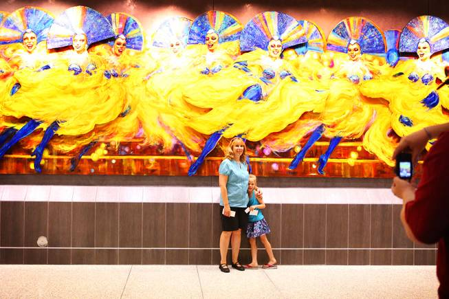 "Sheila Newcomb of Las Vegas poses for a photo with her daughter Lily, 6, in the U.S. Customs and Border Protection area during an open house at the new Terminal 3 at McCarran International Airport in Las Vegas on Saturday, June 9, 2012. Terry Ritter's ""Folies in Flight"" artwork is seen in the background."
