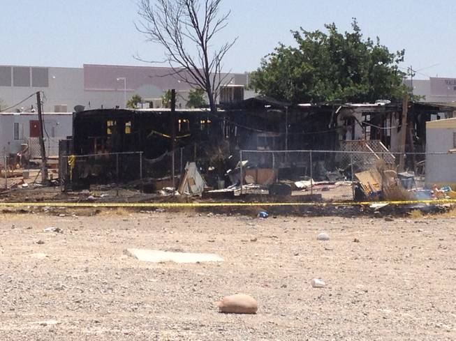 Charred hulls of two mobile homes can be seen from Las Vegas Boulevard North, where a morning fire Friday, June 15, 2012, killed three children, all under the age of 3.
