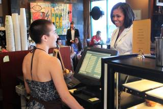 First lady Michelle Obama orders an iced tea from Ria Farmer at Sunrise Coffee Shop during a campaign stop in Henderson Tuesday, June 19, 2012.