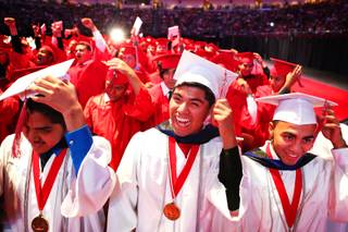 Advanced honors students Freddy Santiago, from left, Liborio Chicas and Kevin Omar Alfaro Martinez move their tassles during the Western High School commencement ceremony at the Orleans Arena on Wednesday, June 20, 2012.
