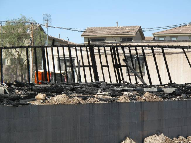Two melted portable restroom facilities next to an office trailor are seen behind scorched wood on the location at an apartment construction site. Fire crews responded to an early morning fire at 1131 Wigwam, the future site of Theory Apartments on Wednesday , June 20, 2012.