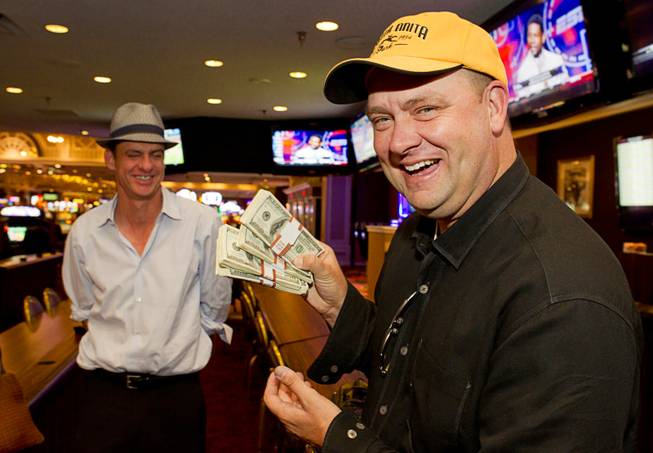 Doug O'Neill, trainer of Kentucky Derby winner I'll Have Another, displays his winnings after cashing a 200-to-1 future bet on the horse at Primm Valley Casino in Primm, Nev. Monday, June 25, 2012. O'Neill won $20,000 for his $100 bet, which he made in February, that the horse would win the Kentucky Derby. At left is Mark Verge, CEO of Santa Anita Park racetrack.