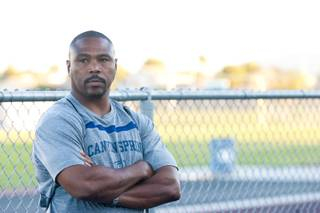 Canyon Springs HS football coach Hunkie Cooper waits for his players to arrive before starting an 8 mile run that will take them to the homeless shelter, Shade Tree, and Woodlawn Cemetery, June 25, 2012.