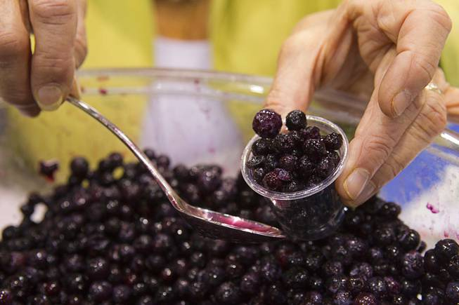 Jeanne Sauve of the Wild Blueberry Association scoops a sample of wild blueberries during the IFT Food Expo at the Las Vegas Convention Center, June 25, 2012. The wild blueberries are higher in antioxident properties than farmed blueberries, she said.