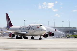 A Virgin Atlantic passenger jet, the first plane to arrive at Terminal 3, is welcomed with a water cannon salute during the opening day of the new terminal at McCarran International Airport Wednesday, June 27, 2012.