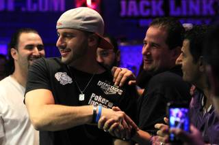 Michael Mizrachi is congratulated by friends after winning the 2012 World Series of Poker $50,000 Players Championship.