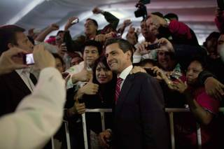 Enrique Peña Nieto, presidential candidate for the Revolutionary Institutional Party (PRI), center, poses for photos with supporters at the party's headquarters in Mexico City, early Monday July 2, 2012. Mexico's old guard sailed back into power after a 12-year hiatus Sunday as the official preliminary vote count handed a victory to Peña Nieto, whose party was long accused of ruling the country through corruption and patronage.