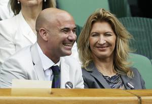 Retired tennis players and husband-and-wife Andre Agassi and Steffi Graf attend a quarterfinals match between Mikhail Youzhny of Russia and Roger Federer of Switzerland at the All England Lawn Tennis Championships at Wimbledon, England, on July 4, 2012.