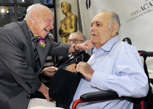 "Mickey Rooney, left, a cast member in the 1963 film ""It's a Mad, Mad, Mad, Mad World,"" greets fellow cast member Jonathan Winters the kick-off of The Last 70mm Film Festival presented by the Academy of Motion Picture Arts and Sciences, Monday, July 9, 2012, at the Samuel Goldwyn Theater in Beverly Hills, Calif."