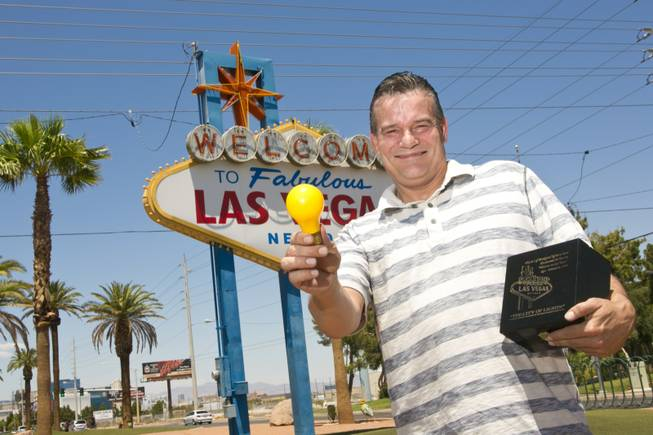 "Russell Millar shows off a souvenir lightbulb that he sells, which came right off the famous ""Welcome To Las Vegas"" sign behind him, Monday July 9, 2012."