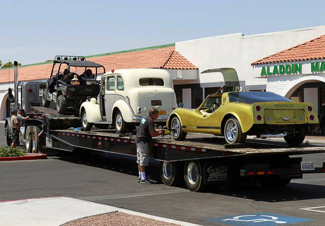 "An HBO crew secures cars, once owned by Liberace, onto a car carrier at the Liberace Museum parking lot, Wednesday July 11, 2012. The cars, a 1972 custom Bradley GT and a 1957 London taxi, are on loan to HBO for a project titled ""Behind the Candelabra,"" an official said."