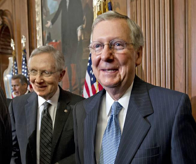 Senate Majority Leader Harry Reid of Nevada, left, and Senate Minority Leader Mitch McConnell of Kentucky attend a ceremony at the U.S. Capitol building on July 11, 2012, in Washington.