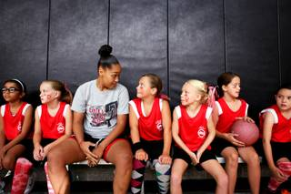 Lady Rebel Kelli Thompson sits with the 'Lil Lady Rebels under 10 team during a girls youth summer basketball league game at the Downtown Recreation Center in Henderson  on Thursday, July 12, 2012.