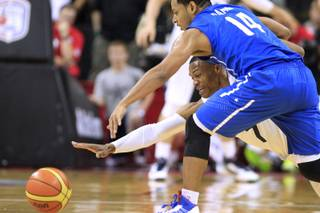 U.S. Olympic basketball team's Russell Westbrook and the Dominican Republic's Ronald Ramon lunge for a loose ball during their exhibition game Thursday, July 12, 2012 at the Thomas & Mack Center. The U.S. won 113-59.