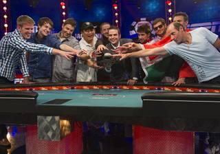Members of the October Nine reach for the championship bracelet held by Jack Effel, World Series of Poker tournament director, after making the final table in the World Series of Poker's $10,000 buy-in, no-limit Texas Hold'em main event at the Rio Monday, July 17, 2012. From left are: Russell Thomas, Jacob Balsiger, Jeremy Ausmus, Steven Gee, Greg Merson, Jesse Sylvia, Robert Salaburu, Andras Koroknai and Michael Esposito. All the players are from the United States except Koroknai who is from Hungary.