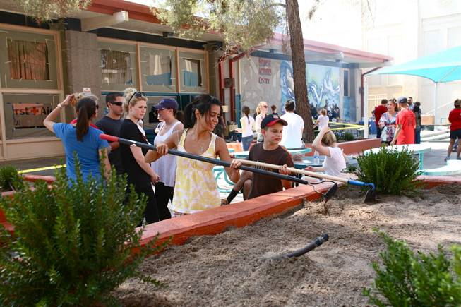 Volunteers refurbish planters and benches in the courtyard of Las Vegas Academy as part of the Downtown Cares day of service on Saturday, July 14, 2012.