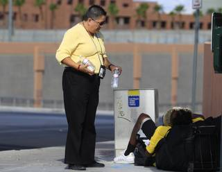 Mindy Torres from HELP of Southern Nevada distributes water to the homeless Thursday, July 19, 2012.