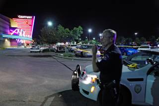 An Aurora Police officer talks on his radio outside of the Century 16 theater at Aurora Mall where as many as 14 people were killed and many injured at a shooting at the Century 16 movie theatre in Aurora, Colo., Friday, July 20, 2012.