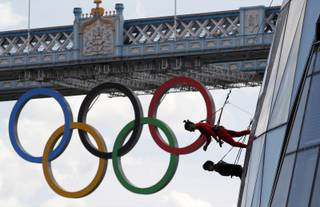 Backdropped by Tower Bridge, dancers perform hanging from outside the City Hall in London as part of London 2012 Olympic Festival, Sunday, July 15, 2012. (AP Photo/Sang Tan)