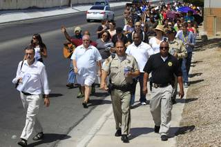 A group of Metro officers and congregants from various Christian churches march down Karen Avenue on a prayer walk Saturday, July 21, 2012.