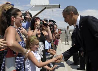 President Barack Obama greets people after arriving at the Nevada Air National Guard at Tahoe International Airport in Reno, Nev., Monday, July 23, 2012, before addressing the VFW national convention.